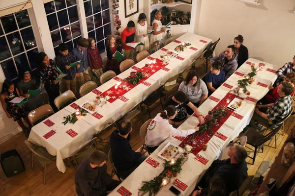 Dinner guests watching Second Home Choir sing Christmas Carols